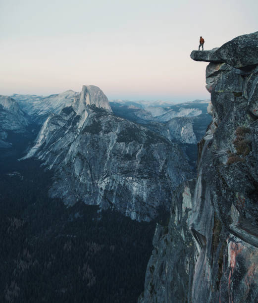 a fearless hiker is standing on an overhanging rock enjoying the view towards famous half dome at glacier point, yosemite national park, california, usa - vintage spitze stock-fotos und bilder