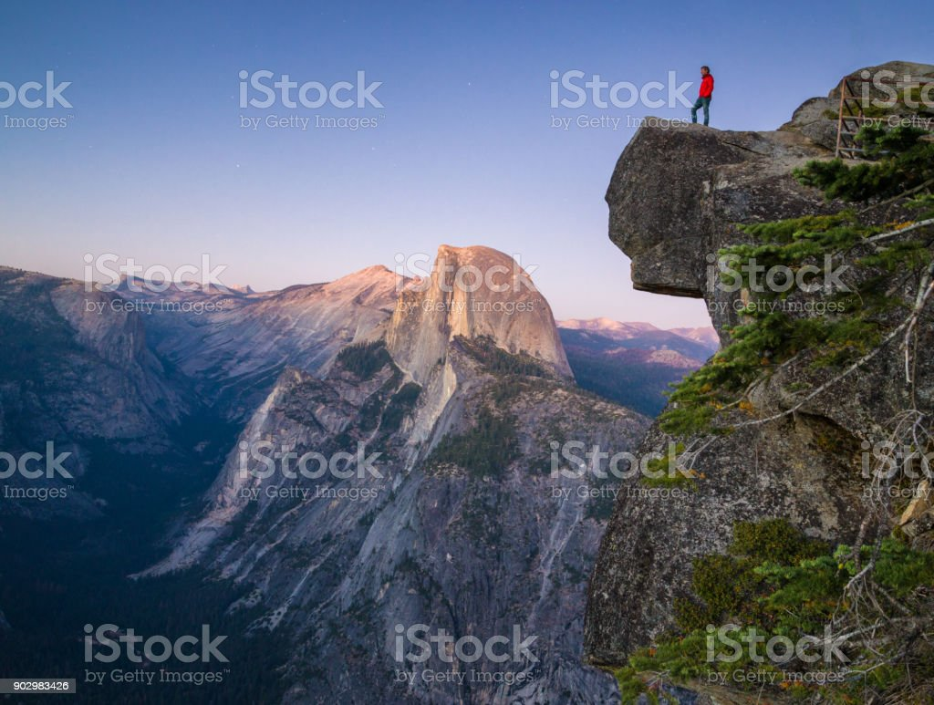 Ein furchtloser Wanderer steht auf einem überhängenden Felsen genießen den Blick in Richtung der berühmten Half Dome am Glacier Point, Yosemite-Nationalpark, Kalifornien, USA – Foto