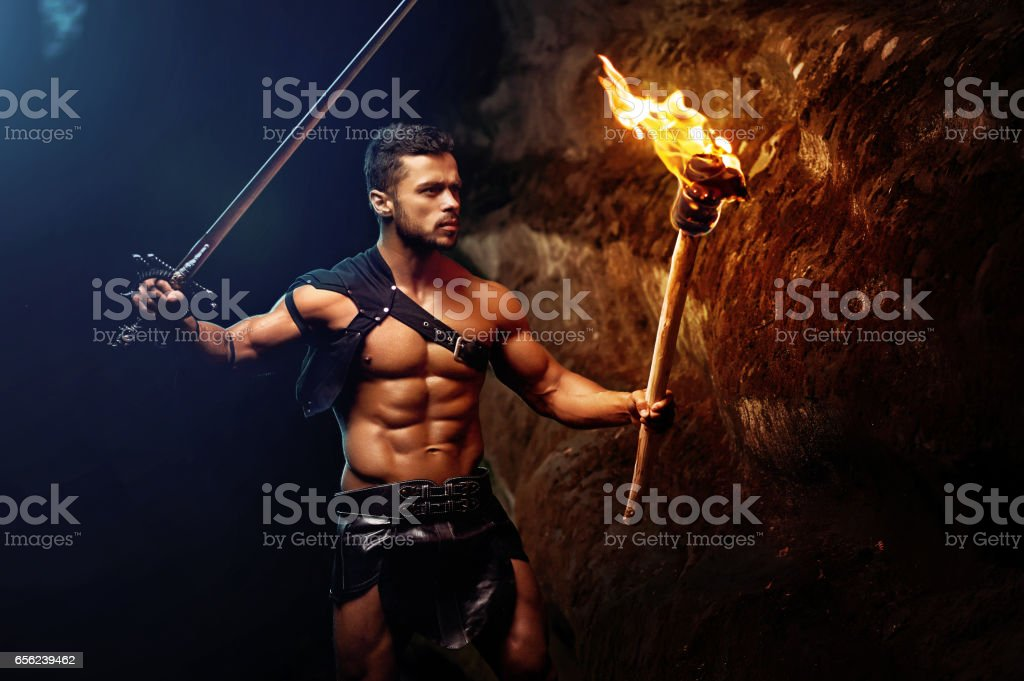 Fearless young muscular warrior with a torch in the dark stock photo
