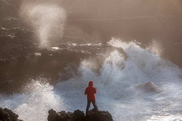 Fearless young photographer surrounded by raging waves at rocky Oregon coast stock photo