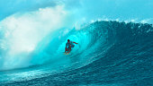 CLOSE UP: Fearless young surfboarder rides inside a spectacular barrel wave. Breathtaking shot of wild emerald wave curling and splashing over a pro male surfer having fun in sunny French Polynesia.