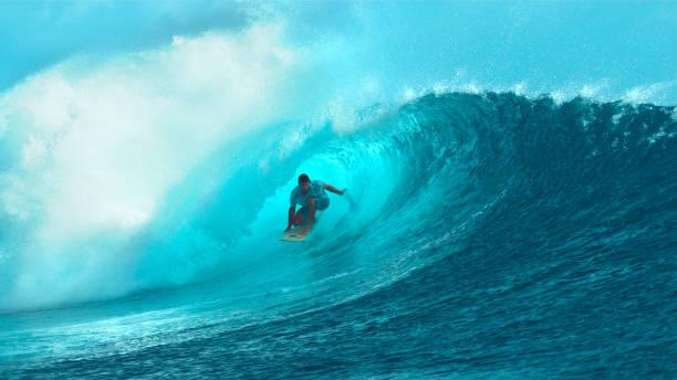 close up: surfboarder jóvenes intrépido paseos dentro de una espectacular cañón de la onda. - surf fotografías e imágenes de stock