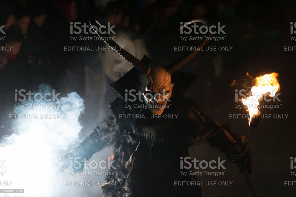 Fearsome Krampus character holding flaming torch and smoke bomb stock photo