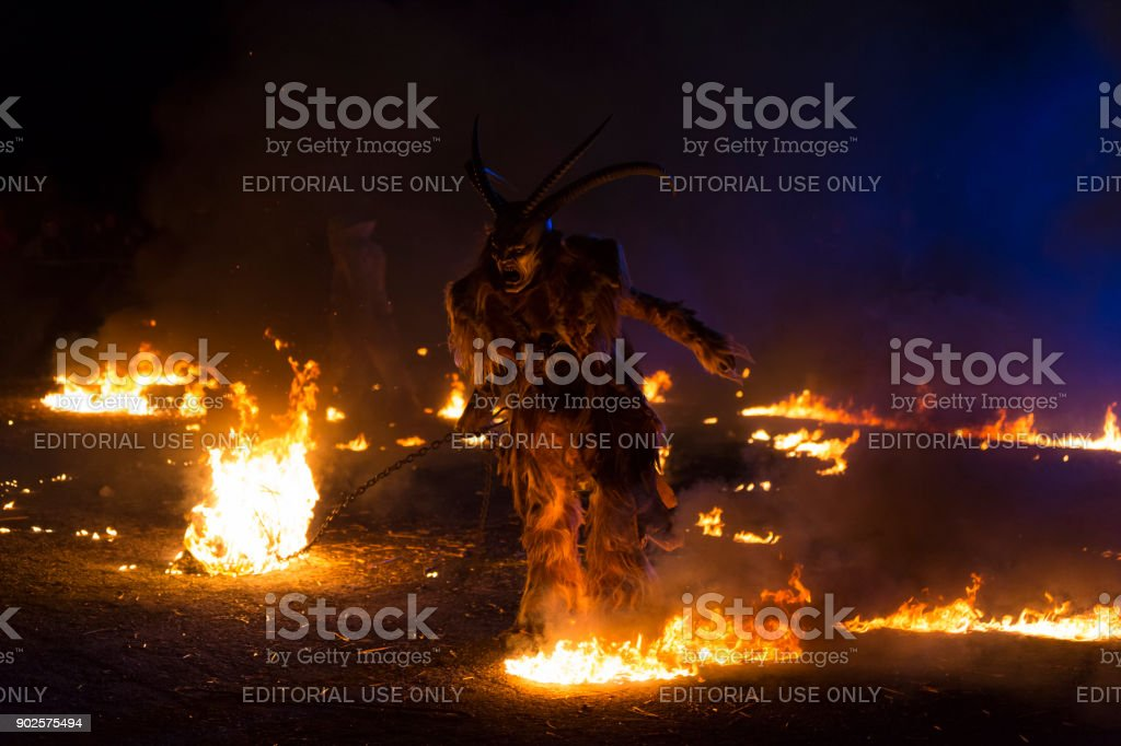 Fearsome Krampus character running around fire stock photo