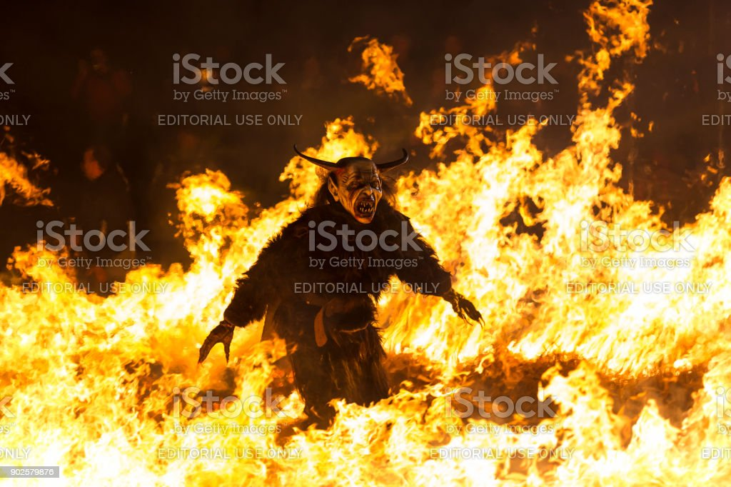 Fearsome Krampus character walking in fire stock photo