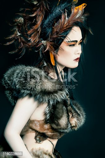 Beautiful Asian woman wearing her black hair up with brown feathers. Wrapped up in fur. Creative make-up and a fierce look. Looking away, dreamy expression.