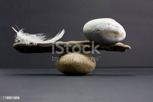 istock feather and stone balance 118951659