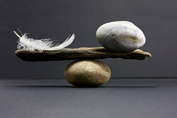 feather and stone balance stock photo