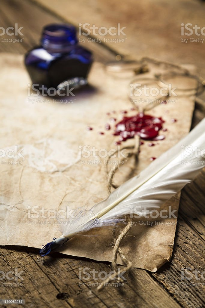 Feather lying on old sheet of paper royalty-free stock photo
