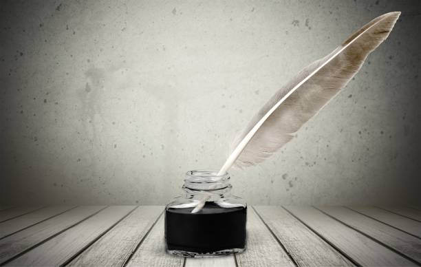 feather quill pen and glass inkwell isolated on background - ink well stock photos and pictures