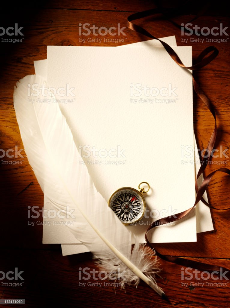 Feather Quill Pen on Blank Paper with a Compass royalty-free stock photo