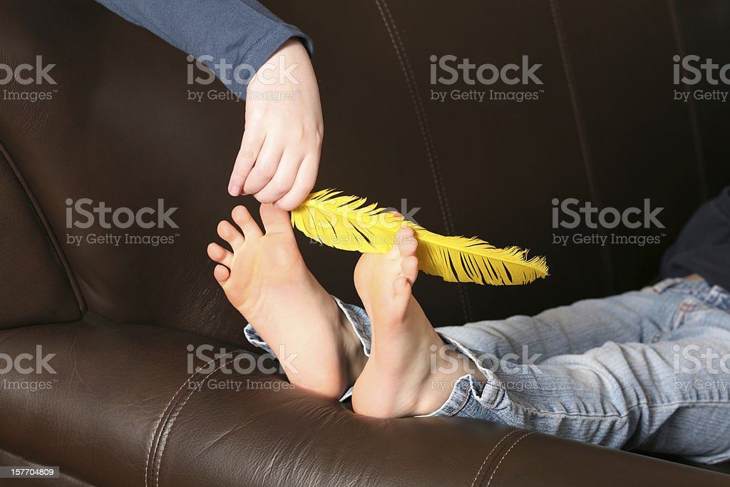 feather tickling bare feet stock photo