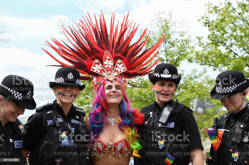 Feathered costume lady with police officers at Gay Pride event stock photo