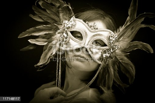 A young girl wearing a feathered mask.