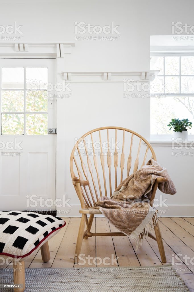 Feature wooden arm chair with throw and cushion ottoman stock photo