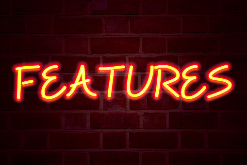 istock Features neon sign on brick wall background. Fluorescent Neon tube Sign on brickwork Business concept for Advertisement Advertising 3D rendered 887670588