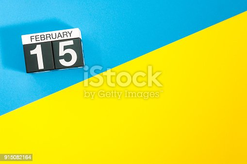 istock February 15th. Day 15 of february month, calendar on blue and yellow background flat lay, top view. Winter time. Empty space for text 915082164