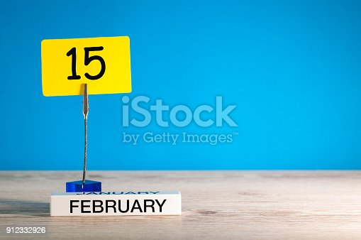istock February 15th. Day 15 of february month, calendar on little tag at blue background. Winter time. Empty space for text, mockup 912332926