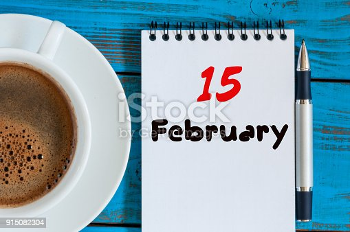 istock February 15th. Day 15 of month, calendar in notepad on wooden background near morning cup with coffee. Winter time. Empty space for text 915082304