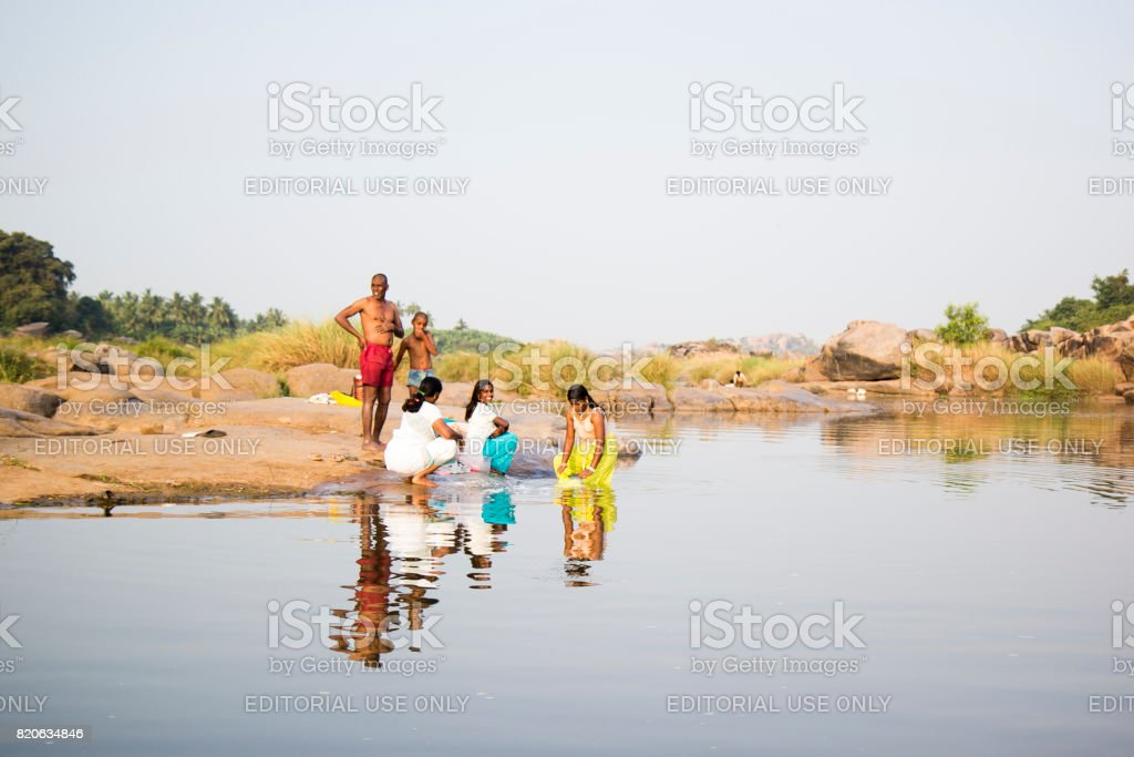 HAMPI, KARNATAKA, INDIA - 19 February 2013 - Happy Indian people at the river colourfully dressed washing clothes. stock photo