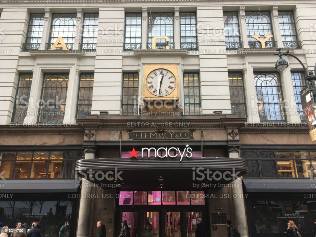 1 February 2017 - New York City: Main entrance to Macy's Department Store with iconic gold clock on a winter afternoon in New York.  Looking up at R H Macy and Co. store in Midtown Manhattan. stock photo