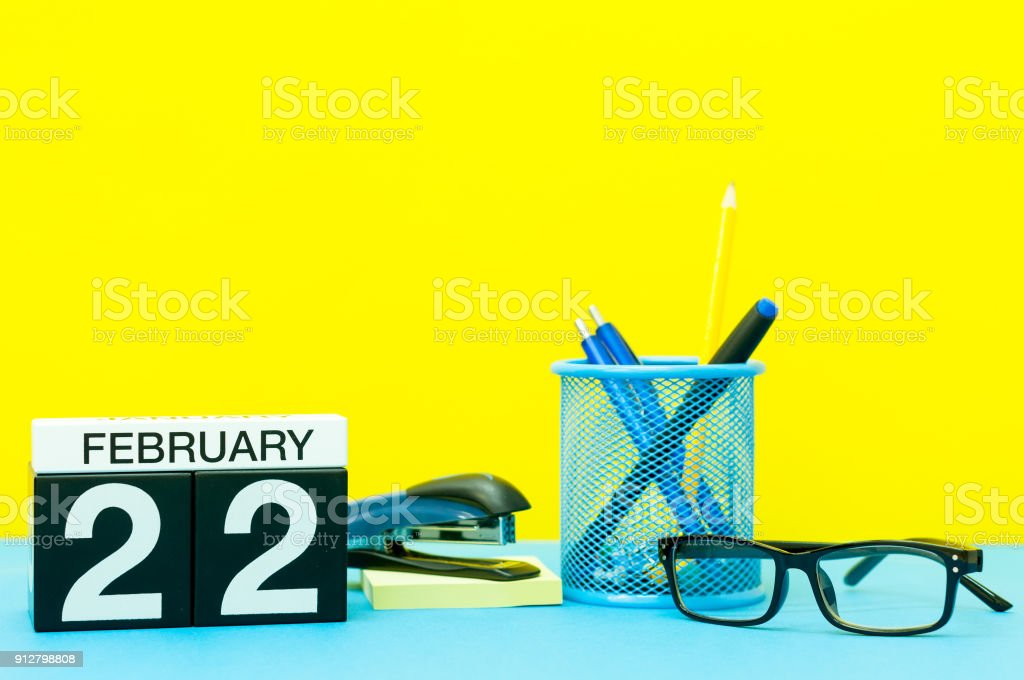 February 22nd. Day 22 of february month, calendar on yellow background with office supplies. Winter time stock photo