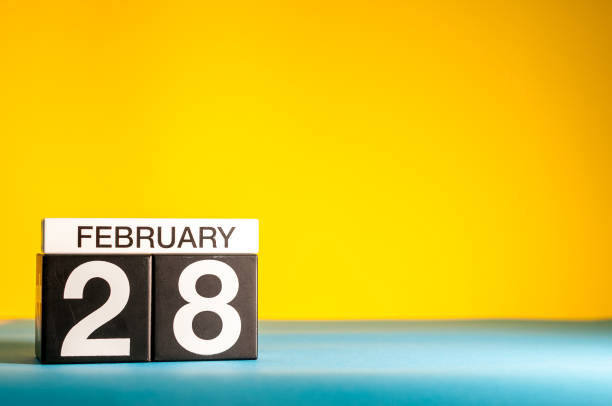 february 28th. day 28 of february month, calendar on yellow background. winter time, leap-year. empty space for text - february stock photos and pictures