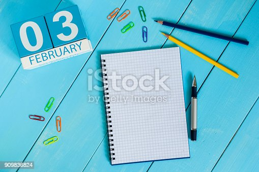 istock February 3rd. Day 3 of month, calendar on wooden workplace background. Winter time. Empty space for text 909836824