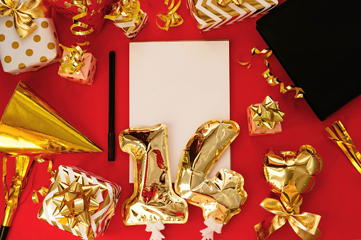 14 February. Lots of gifts, golden 14 balloons, note for Valentine's Day isolated on red background. Holidays concept. The view from the top.