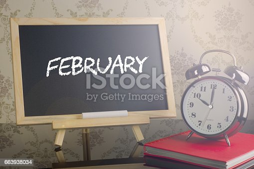 istock February on chalkboard with alarm clock. 663938034