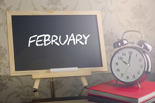 istock February on chalkboard with alarm clock. 663938034