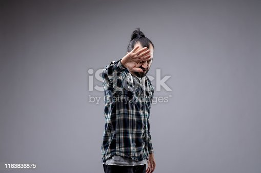 Fed up man holding up his hand in a stop or go away gesture while looking down at the floor indicating he has had enough isolated on grey with copy space