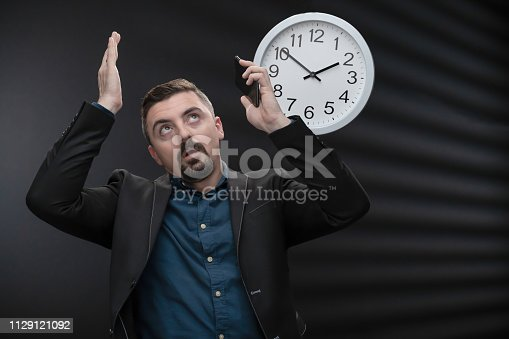 CEO fed up not having enough time to do everything. The man is of caucasian ethnicity and is formally dressed in button down shirt and black jacket. The scene is situated in a studio environment in front of black background. Location of the shoot is Sofia, Bulgaria (Eastern Europe). The picture is taken with SONY A7RIII camera.