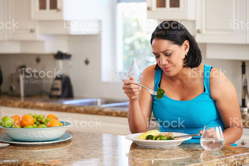 Fed Up Overweight Woman Eating Healthy Meal in Kitchen stock photo
