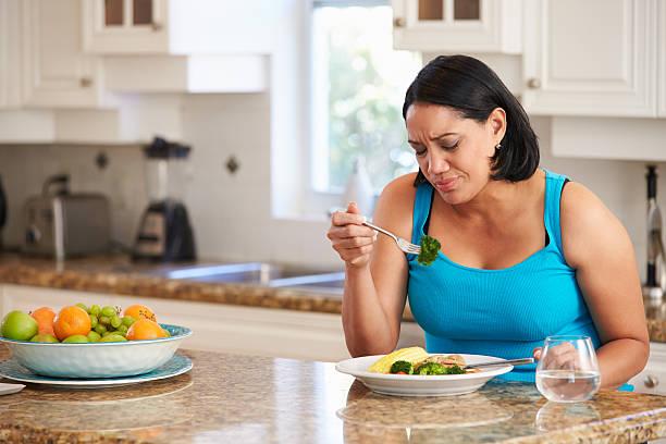 müde, übergewichtige frau essen gesunde mahlzeit in der küche - fett nährstoff stock-fotos und bilder