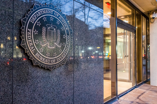 Washington Dc, United States - December 29, 2016: FBI, Federal Bureau of Investigation Headquarters, on Pennsylvania avenue sign with traffic reflections at night