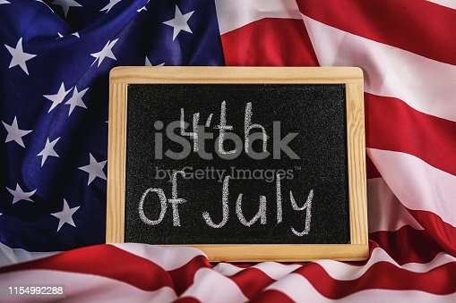 $th of July text written on wooden black chalkboard with USA flag. United States of America stars & stripes patriot veteran remembrance symbol. Background, close up, copy space, top view.
