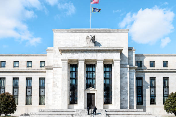 Federal Reserve bank entrance, facade architecture building, wall security guards standing by doors, path, American flags, blue sky Washington DC, USA - March 9, 2018: Federal Reserve bank entrance, facade architecture building, wall security guards standing by doors, path, American flags, blue sky monetary policy stock pictures, royalty-free photos & images
