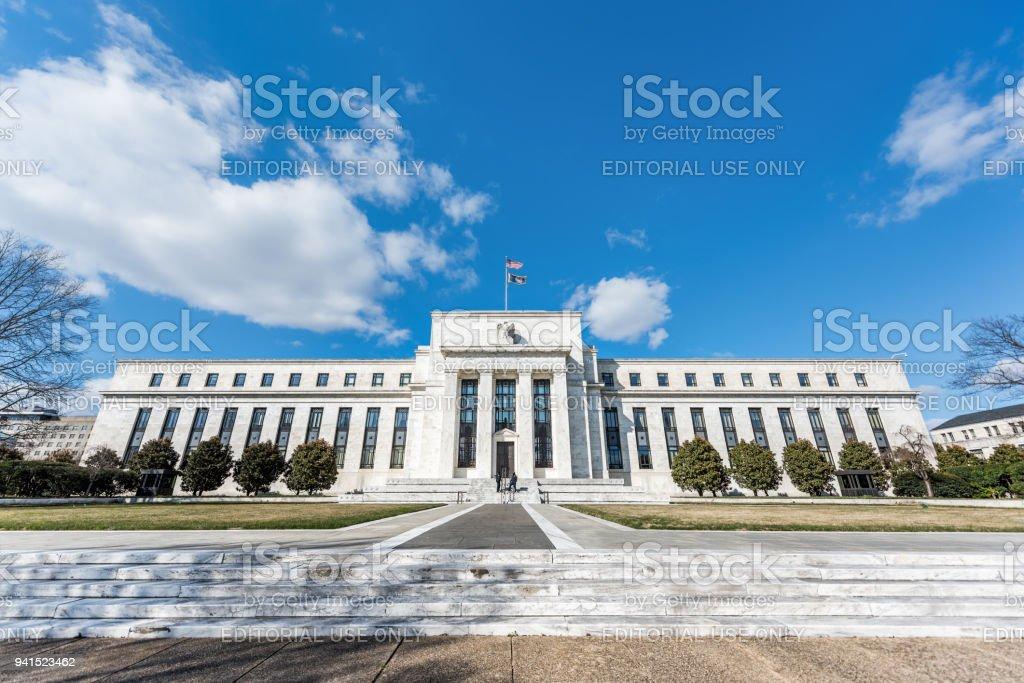 Arquitetura de grande angular de entrada da Reserva Federal construindo portas de segurança de parede, bandeiras americanas, caminho, céu azul - foto de acervo