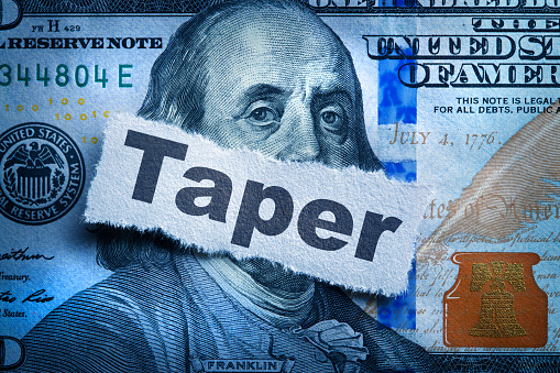 The word taper printed on a torn piece of paper that sits on top of a one hundred dollar bill.