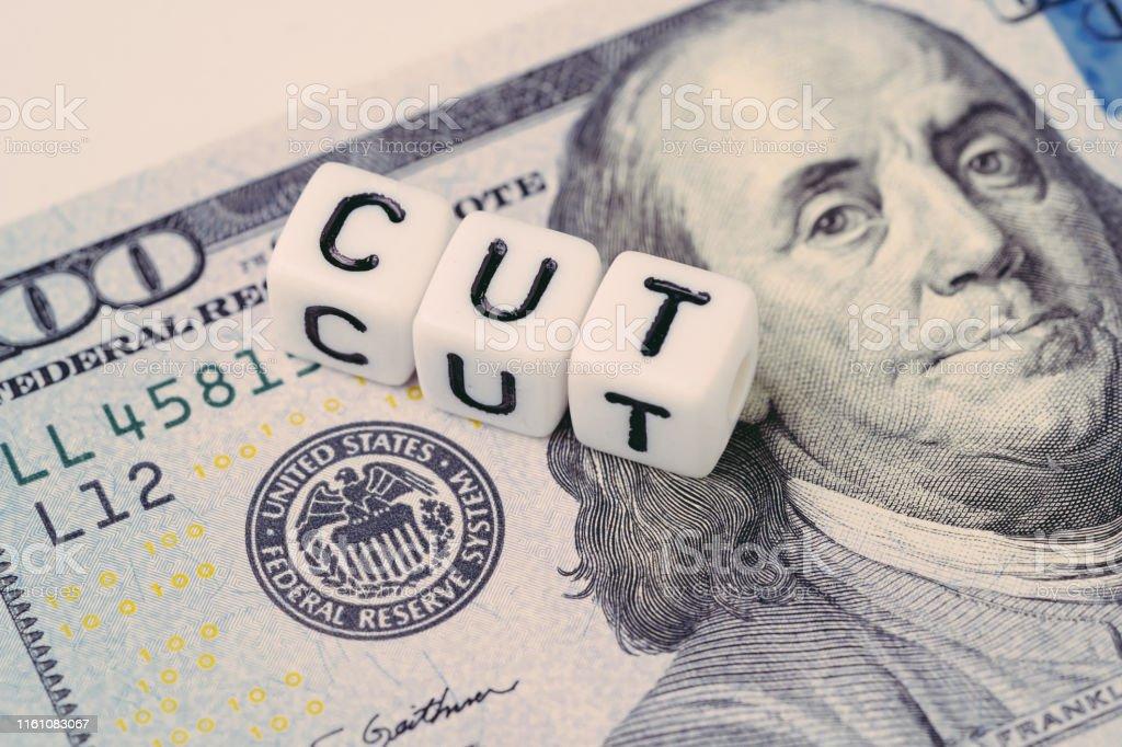 FED,美聯儲與降息概念,小立方體塊與字母構建字CUT旁邊的美聯儲標誌美元鈔票 - 免版稅付錢圖庫照片