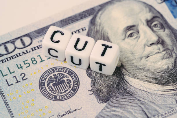 fed, federal reserve with interest rate cut concept, small cube block with alphabet building the word cut next to federal reserve emblem on us dollar banknote - cutter stock pictures, royalty-free photos & images