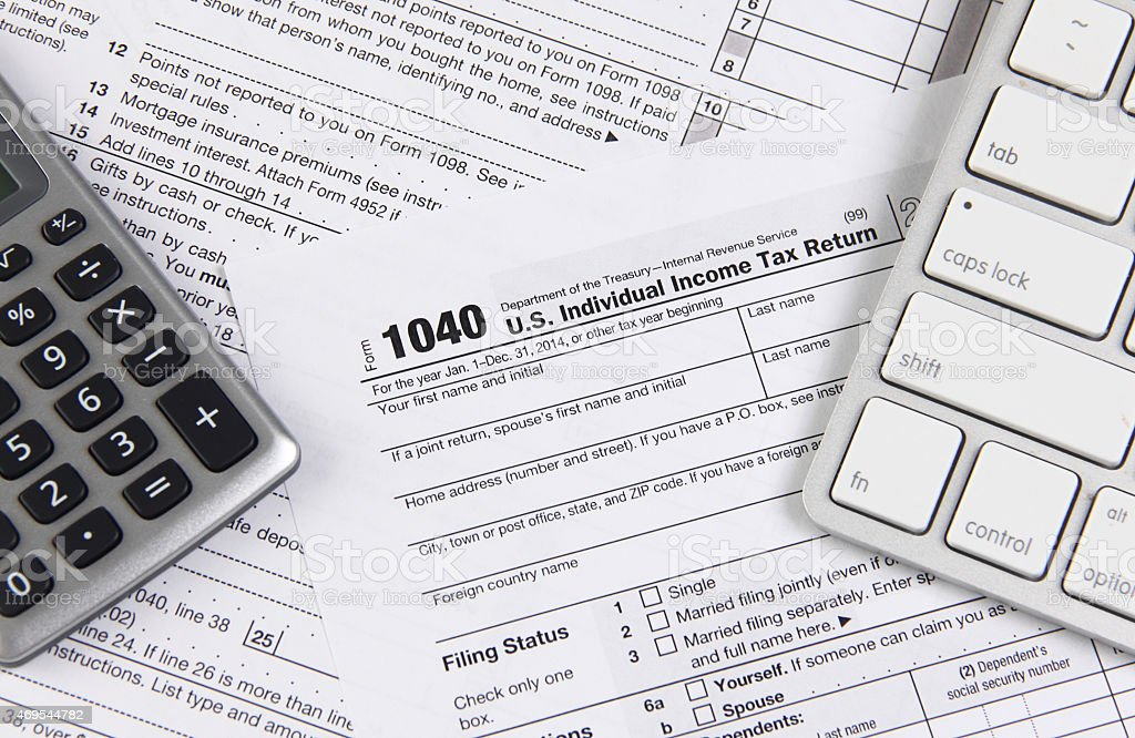 Federal tax form 1040 with keyboard and calculator Concept image for online tax filing. Federal income tax form 1040 on a table with modern technology equipment like computer keyboard and calculator. Image from DSLR camera with minimal post processing 1040 Tax Form Stock Photo
