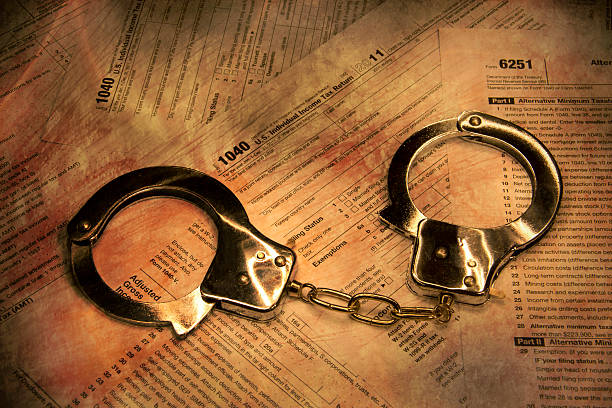 Federal tax fraud concept with handcuffs stock photo