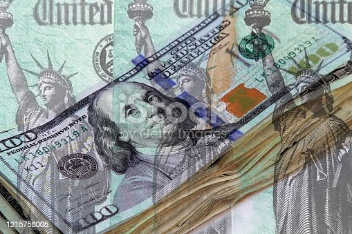 Row of Federal treasury checks over background of a stack of US currency.  Concept image for  government payments for corona virus relief, IRS refund or other financial payments.