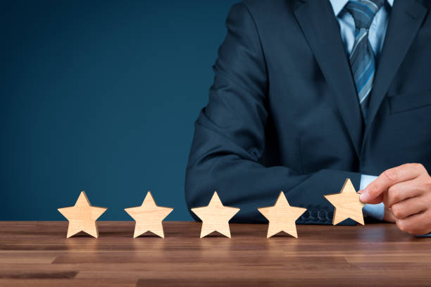 Feedback and rating concept Increase rating, evaluation and classification concept. Businessman sitting behind a table and add fifth wooden star. first class stock pictures, royalty-free photos & images