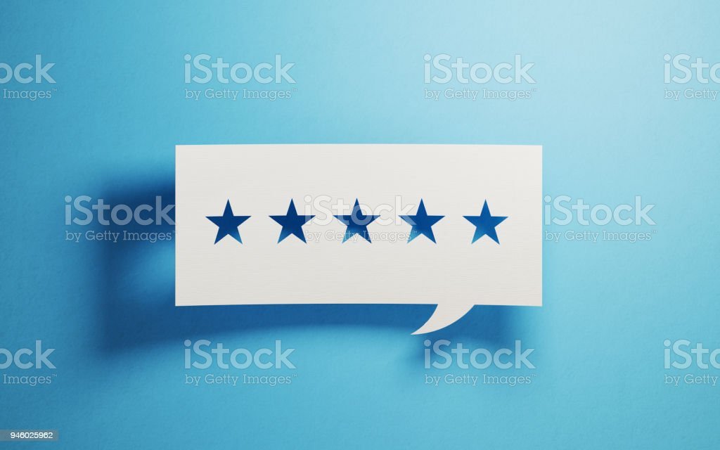 Feedback Concept - White Chat Bubble With Cut Out Star Shapes Over Blue Background stock photo