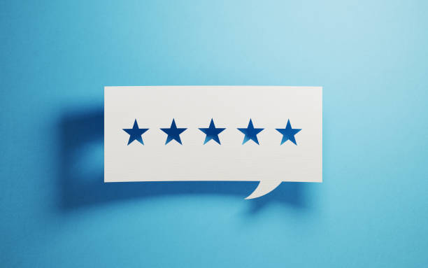 feedback concept - white chat bubble with cut out star shapes over blue background - esaminare foto e immagini stock