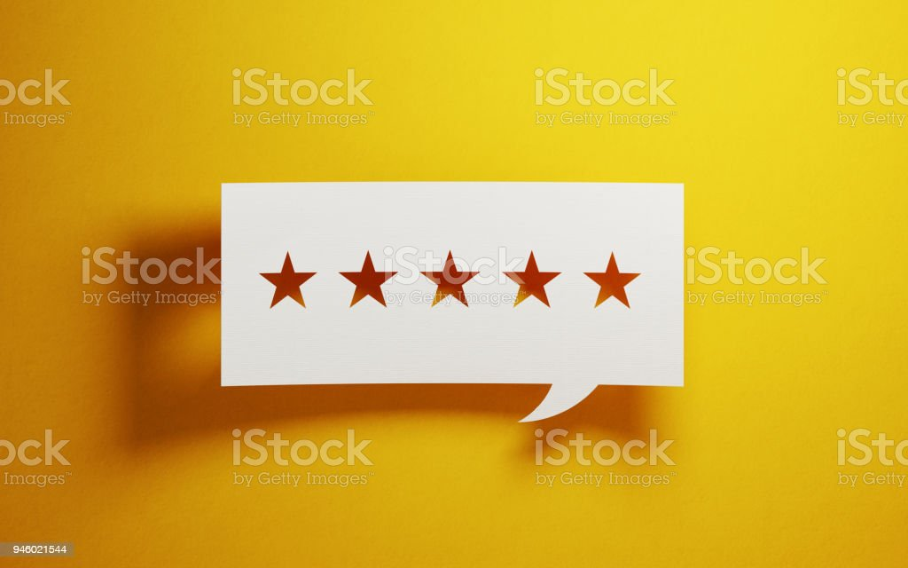 Feedback Concept - White Chat Bubble With Cut Out Star Shapes Over Yellow Background stock photo