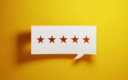 Feedback Concept White Chat Bubble With Cut Out Star Shapes Over Yellow Background Stock Photo - Download Image Now
